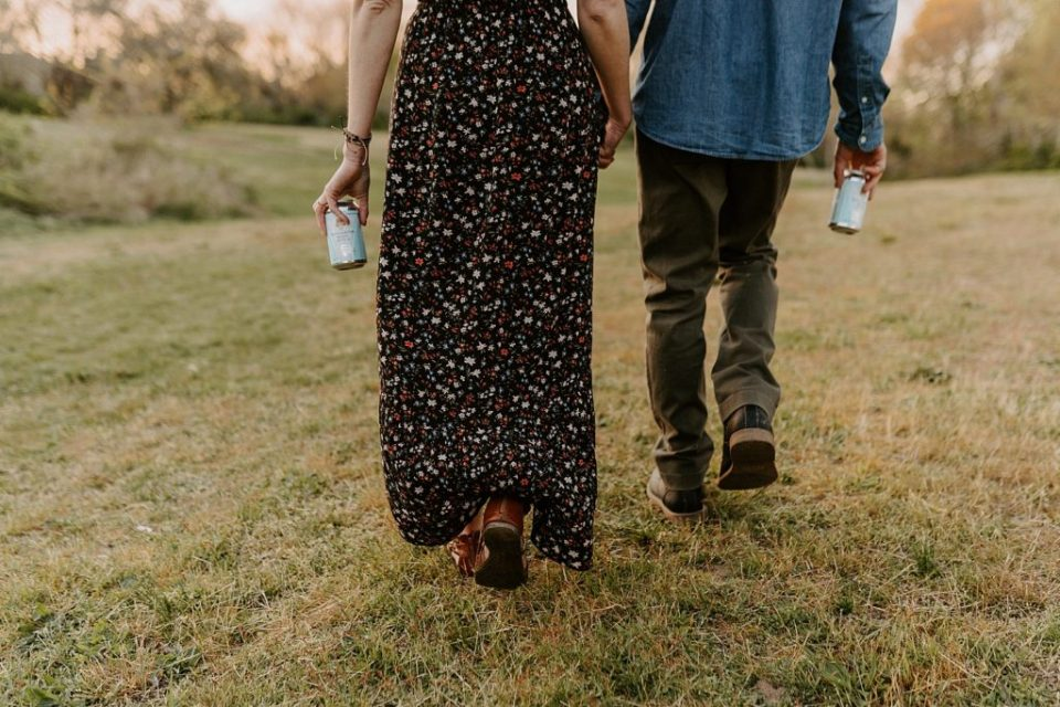 Closeup of couple walking together on grassy field with beer in their hands