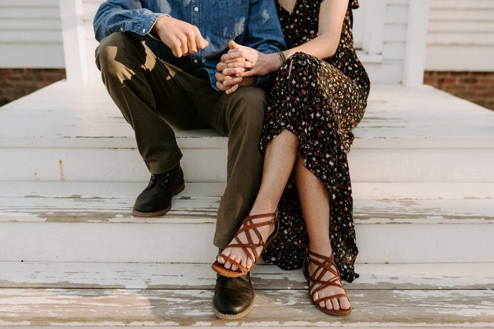 Closeup of couple holding hands sitting on staircase