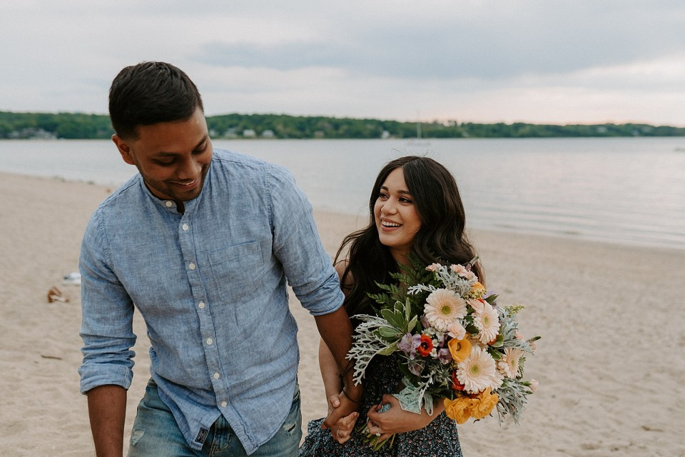 Candid portrait of Couple holding hands walking on the sand with woman holding bouquet