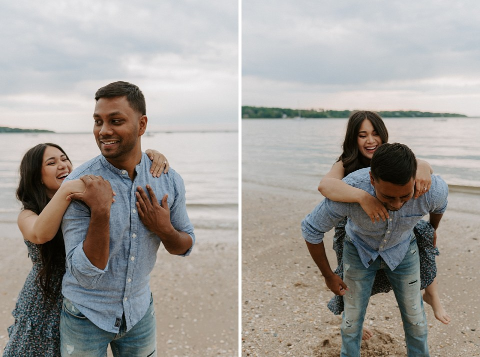 Candid shot of woman getting on man's back to piggy back on the beach