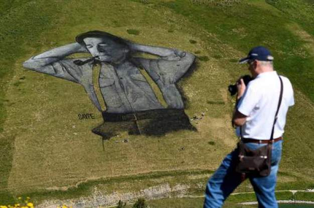 A man photographs a painting, created by French artist Saype and said to be the world's largest biodegradable painting, on the Chaux-de-Mont ski slope above the Alp resort of Leysin on August 4, 2016. The 100 meter long and 100 meter large painting is made with flour, linseed oil, water and biodegradable natural pigments. / AFP PHOTO / Alain Grosclaude / RESTRICTED TO EDITORIAL USE - MANDATORY MENTION OF THE ARTIST UPON PUBLICATION - TO ILLUSTRATE THE EVENT AS SPECIFIED IN THE CAPTION