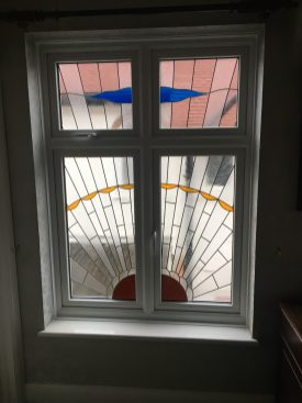 White VEKA PVC window with stained glass design