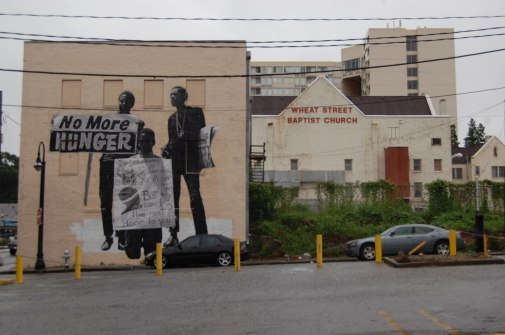 """""""No More Hunger"""" and """"You can do anything, if you try...but can I live next door to you?"""" wheatpasting by artist. J.R. at the intersection of Auburn Ave. and Hilliard Street."""