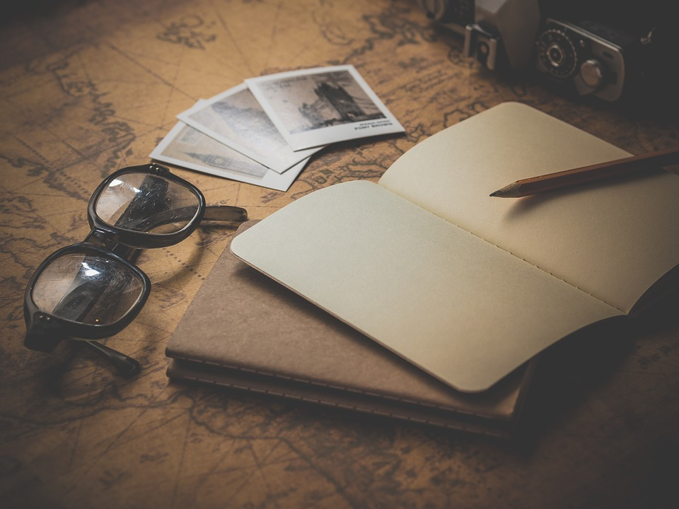 A person plans travels with a notepad and photos