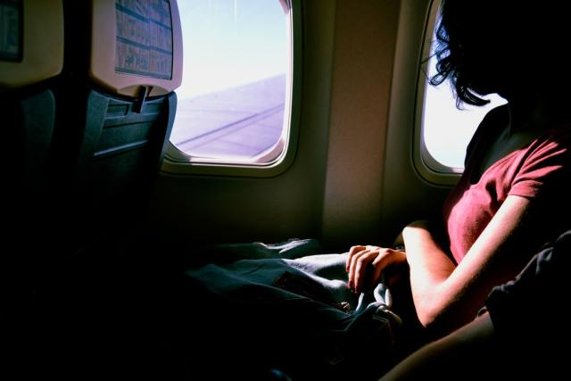 woman sitting on plane looking out of window