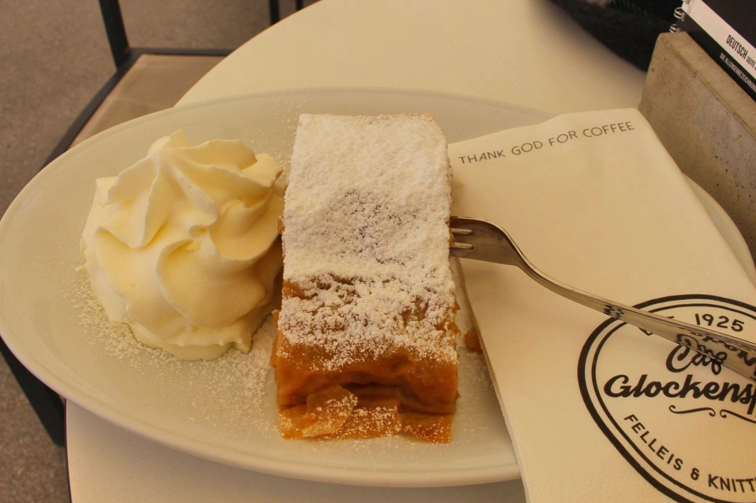 An apple strudel, on a plate alongside a fork and some whipped cream.
