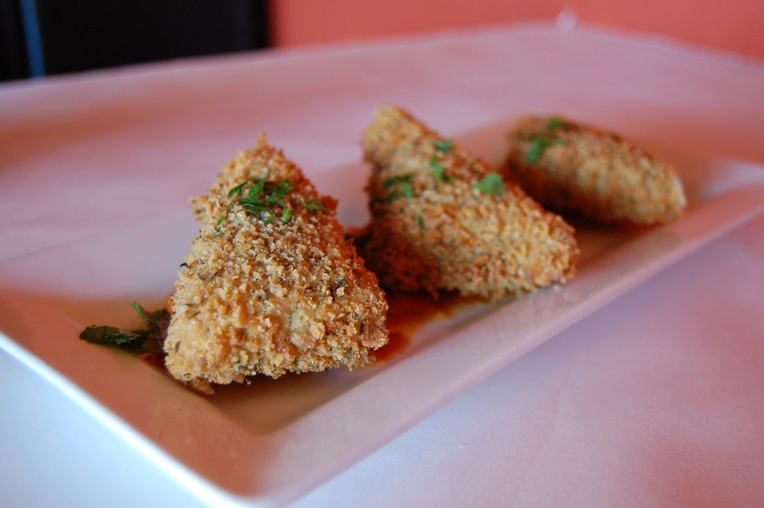 Three pieces of triangular fried cheese with herbs on top