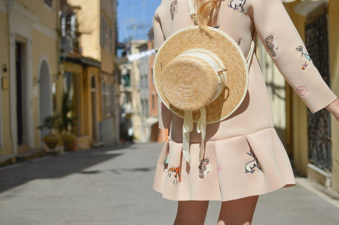 Fashionable woman with a hat attached to her bag walking down a street
