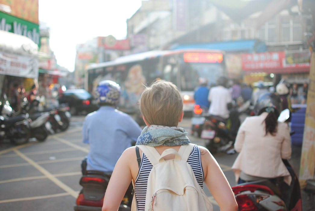 A young woman wearing a backpack walks through a city