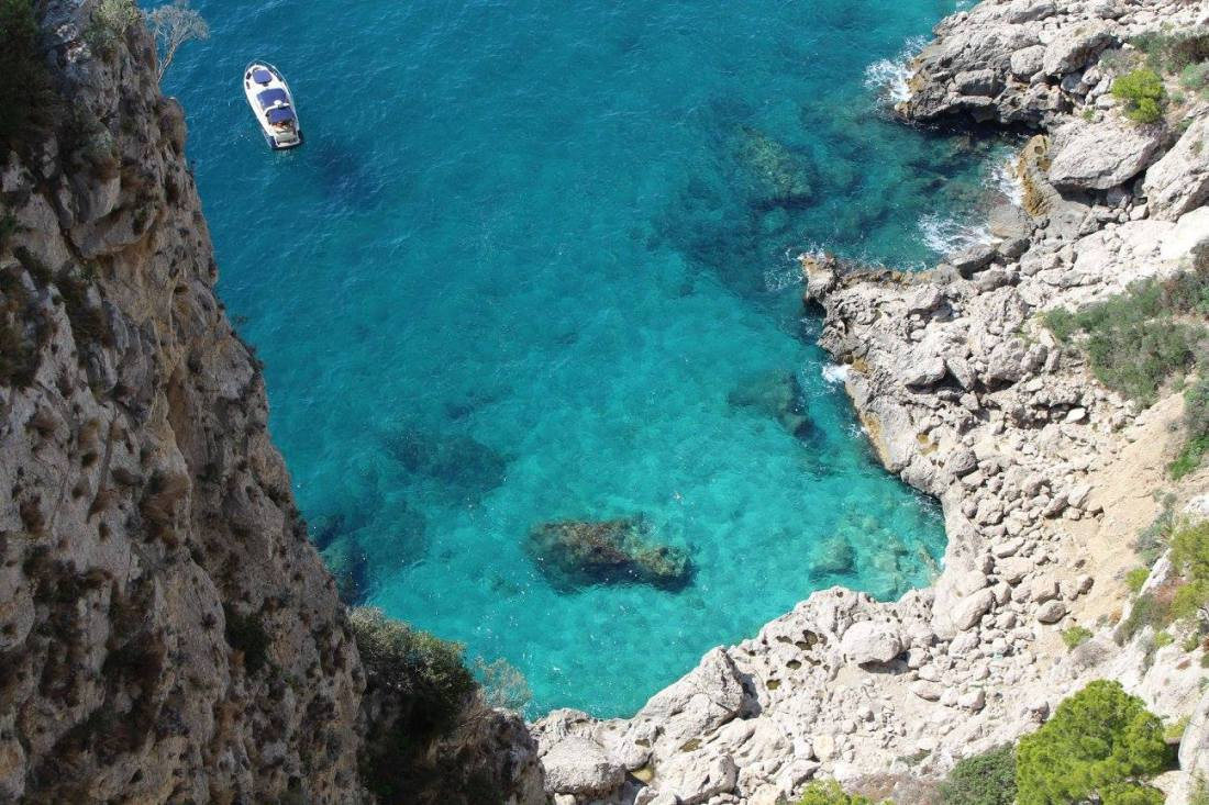 A cove on Capri with a boat bobbing on the water