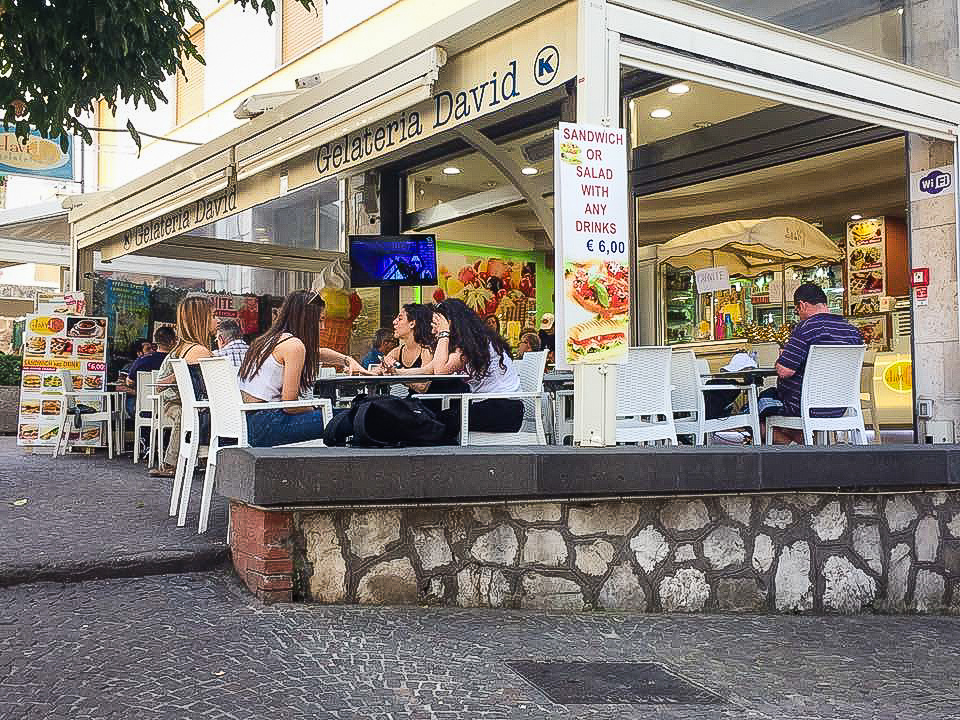 An ice cream bar with customers sitting outside