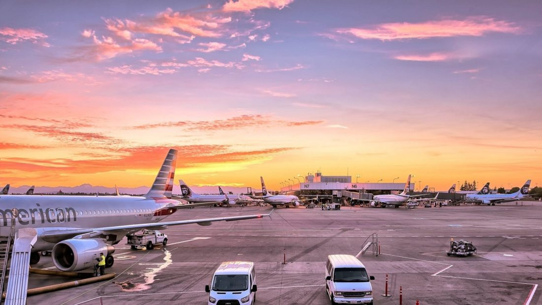 An image of grounded planes against a sunset at an airport