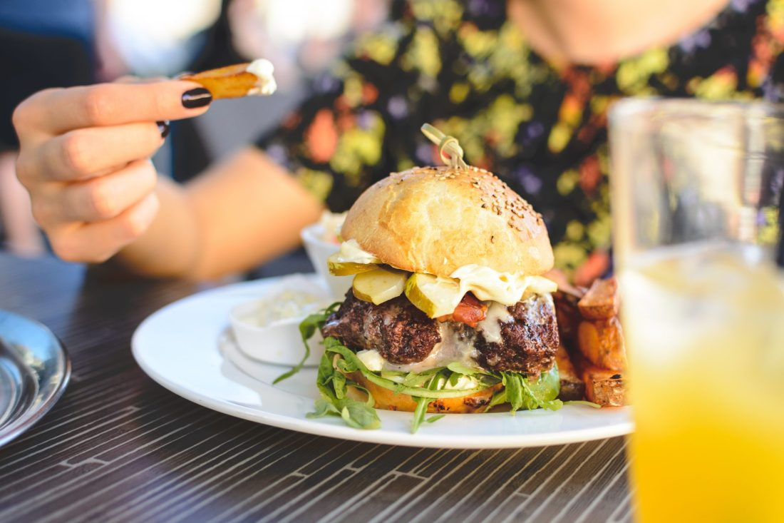 A woman eats a burger with salad