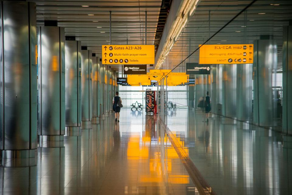 A woman walking down a long corridor at Heathrow Airport