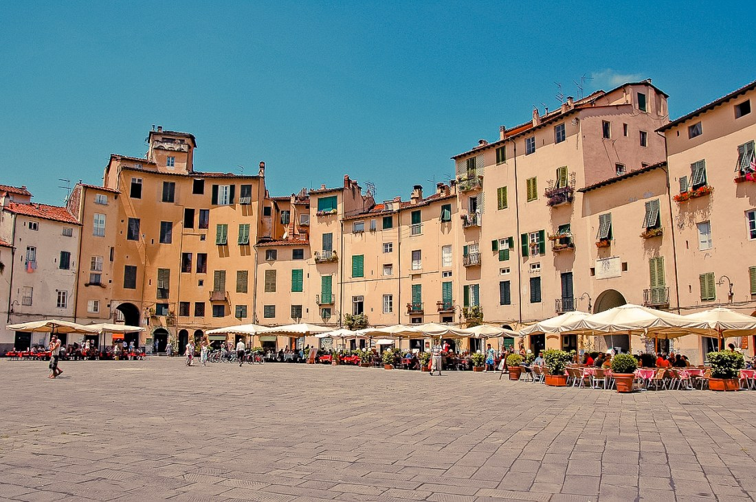 A piazza with umbrellas and tables in Lucca, Italy