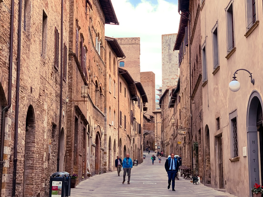 People walk down a medieval street in San Gimignano, Italy