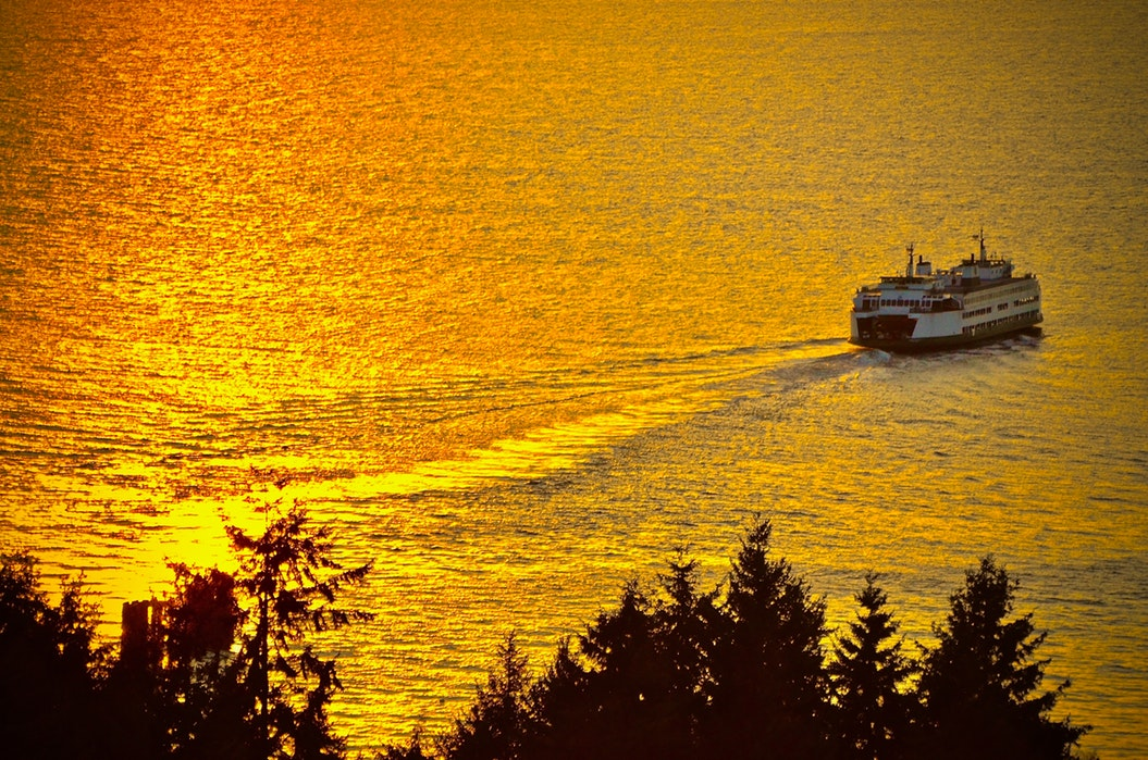 A ferry sails across sunlit water