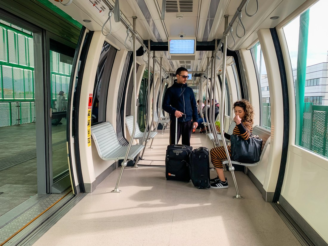 Two people sit on the PisaMover monorail at Pisa Airport