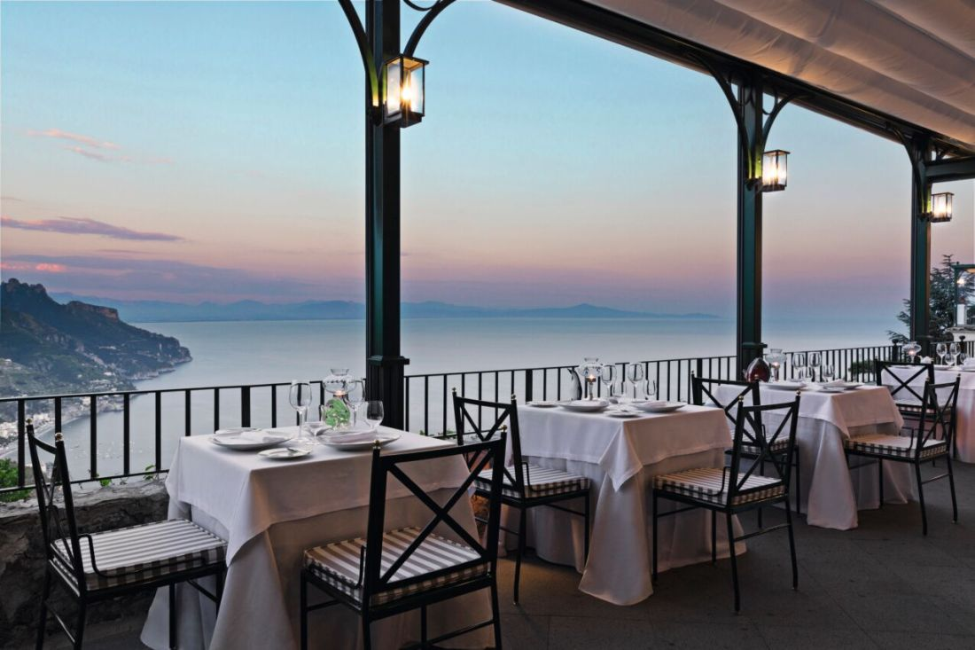 A row of tables are set for dinner on a terrace as the sun sets