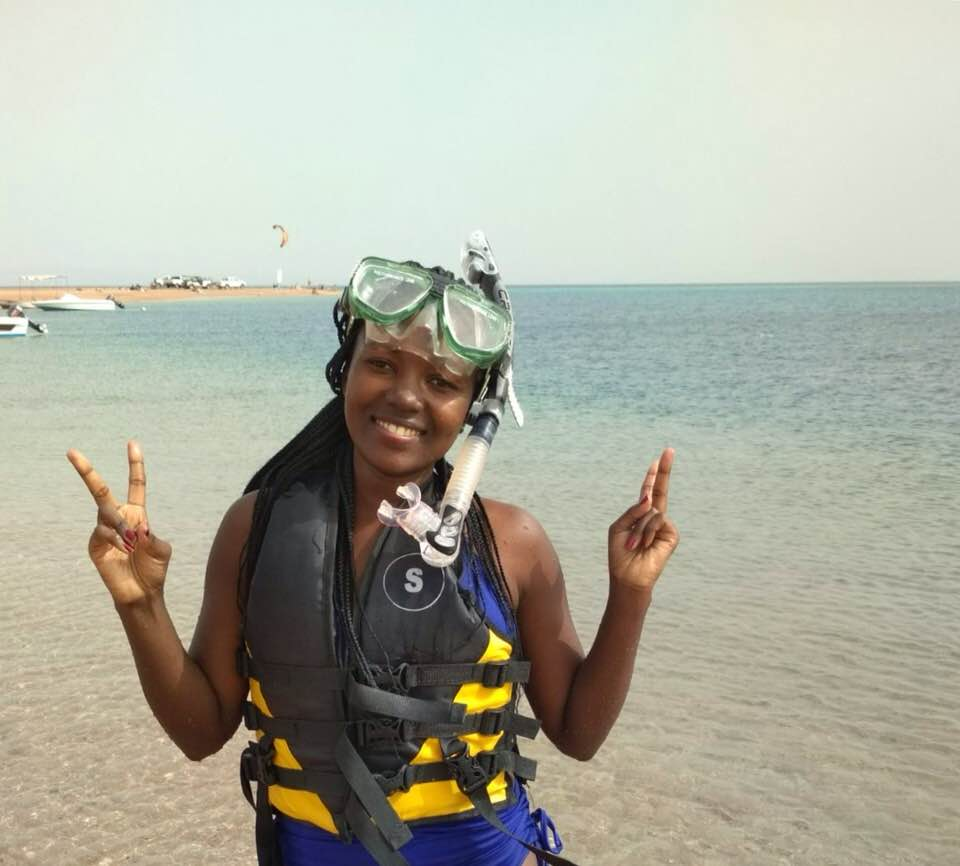 A young woman in snorkelling gear celebrates after a dive