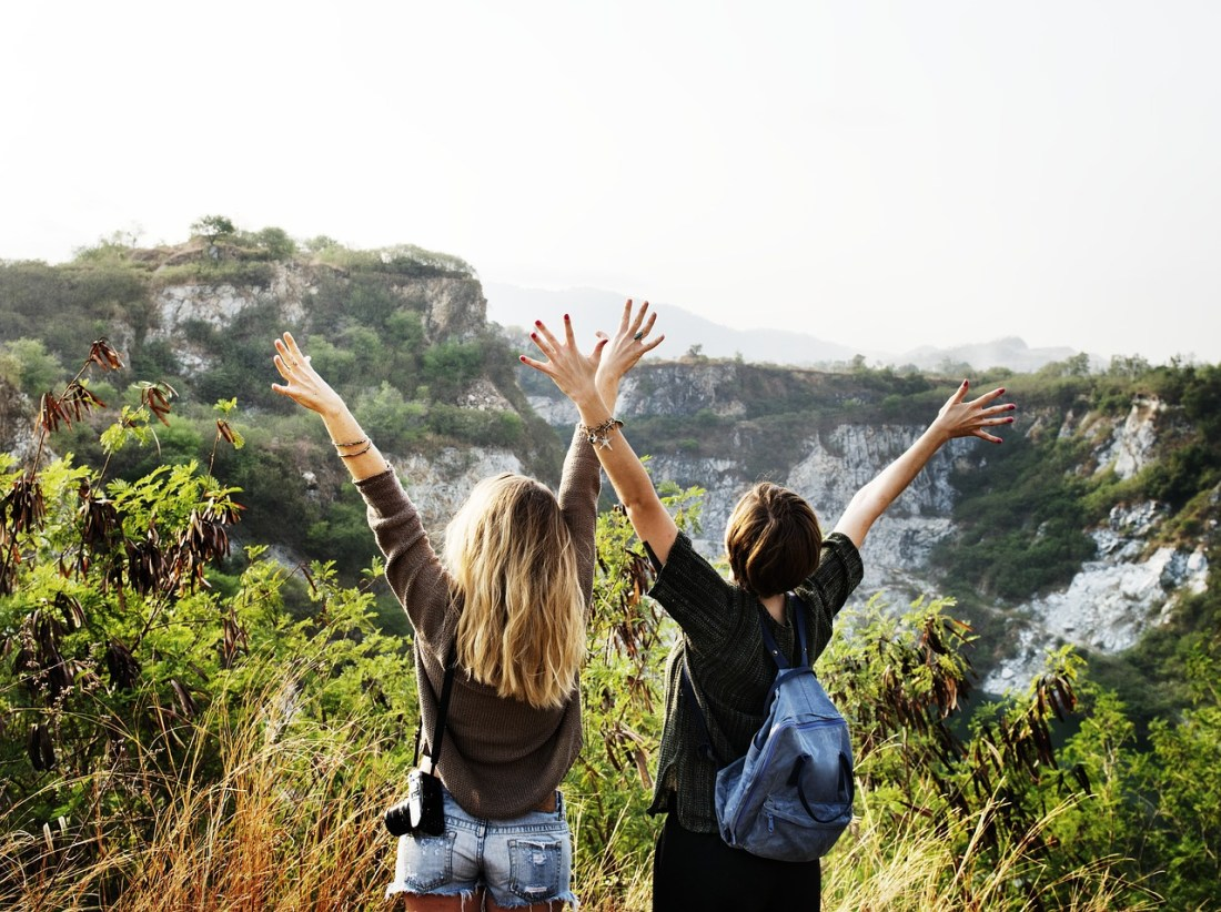 Two women celebrate with arms aloft on a hike - How to Overcome Travel Anxiety - Travel Bloggers' Stories