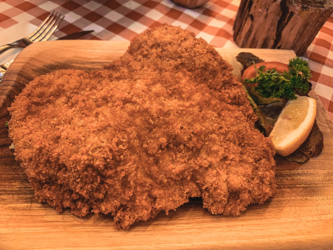 A huge schnitzel, served on a wooden platter
