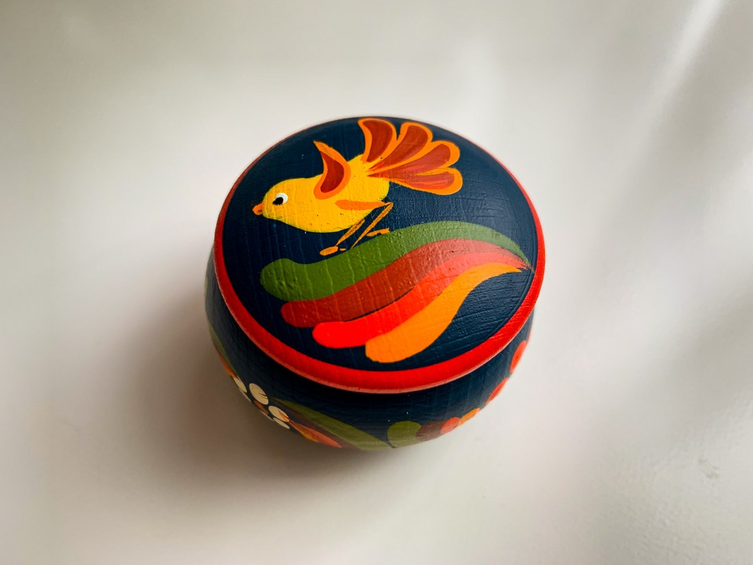 A small wooden box, decorated with a brightly painted bird