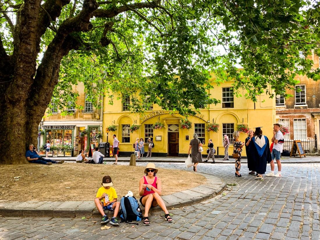 People sit beneath a plane tree in a pretty square in Bath
