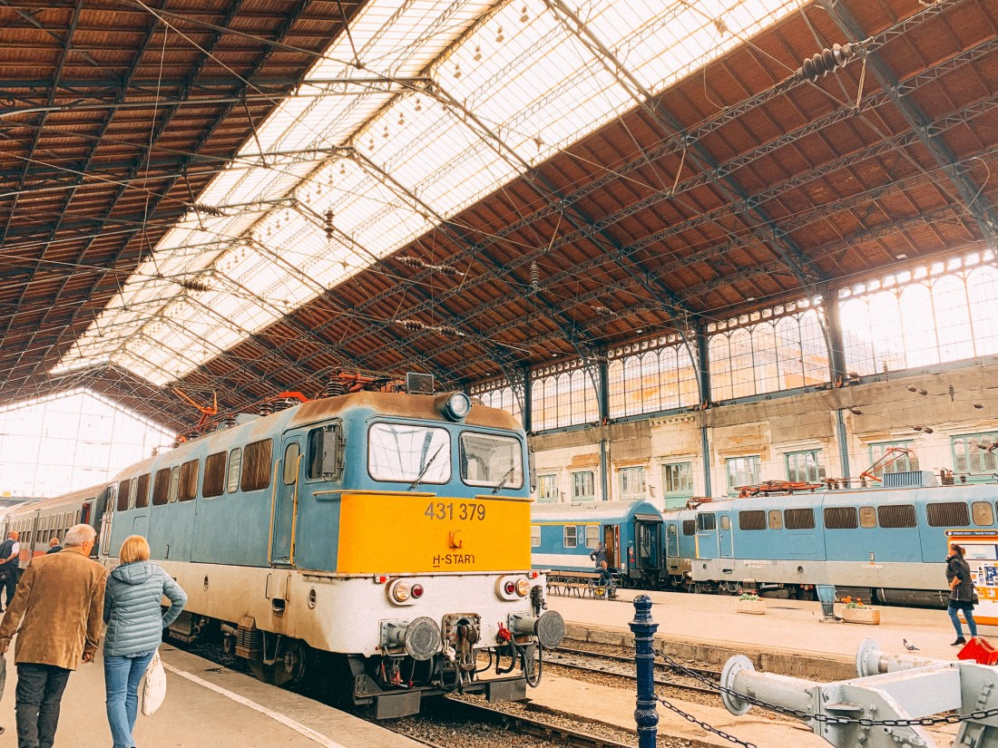 A train rests in the large station at Budapest Nyugati, a key component in how to get to Budapest