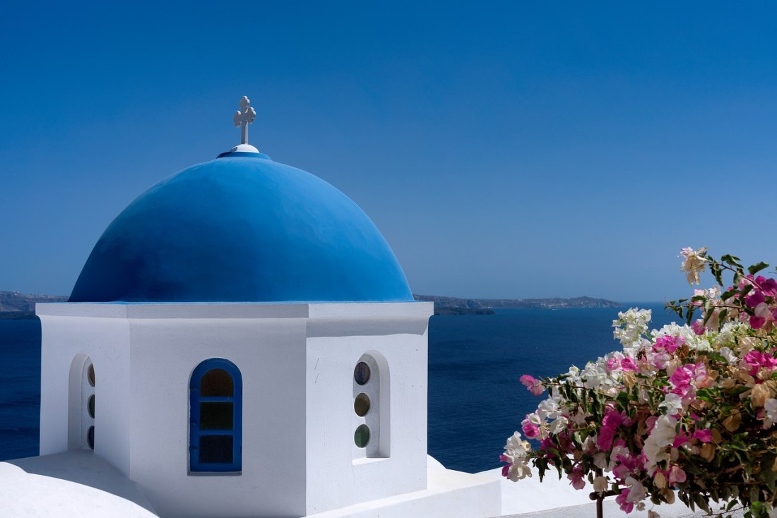 A blue domed Greek building against a blue sky and sea