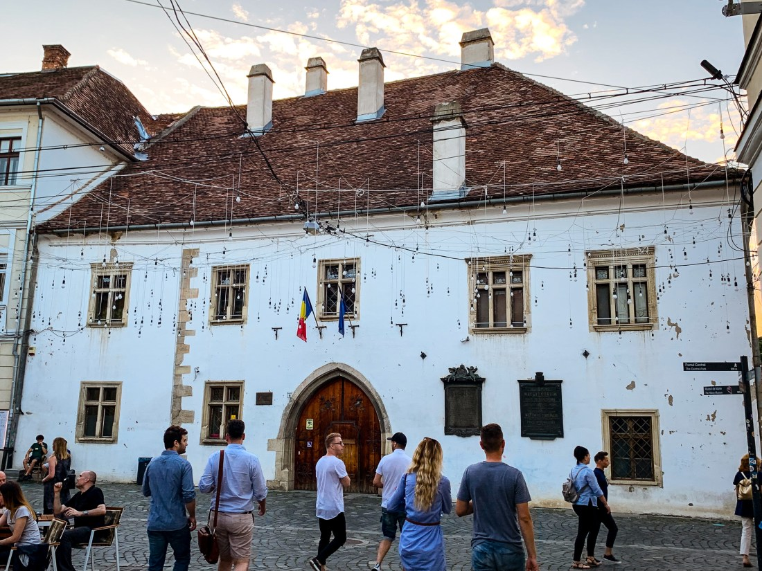 The birthplace of Matthias Corvinus in Cluj is a white building with many windows and a tiled roof