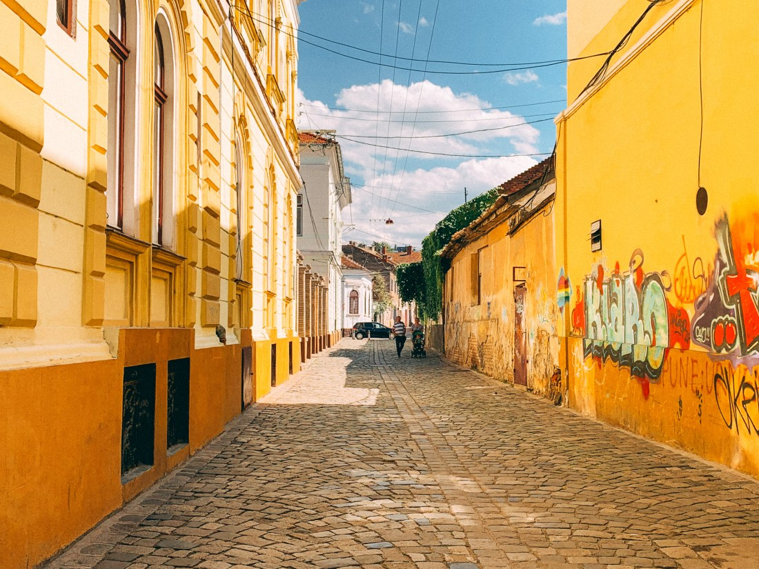A scenic street in Cluj-Napoca, with colourful walls and graffiti.