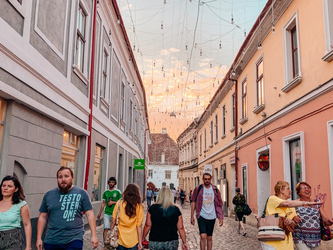 Young people walk through a street with lightbulbs hanging above it at sunset in Cluj - a good example of Cluj nightlife