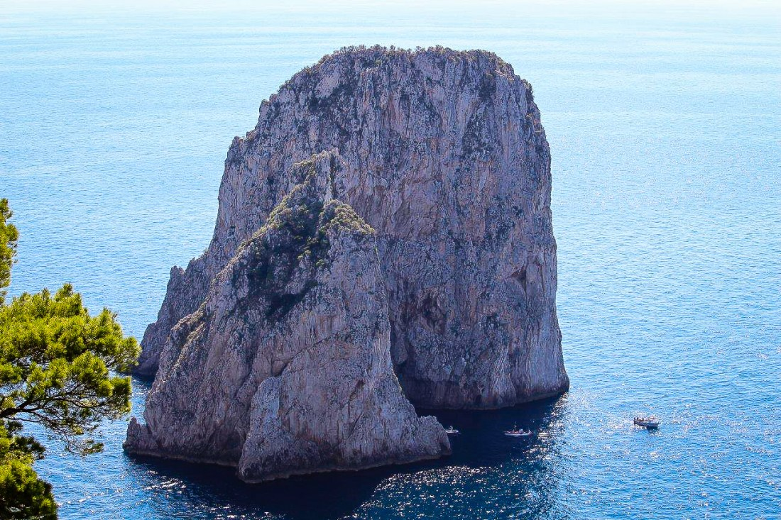 One of the rocks of the Faraglioni, which has a natural arch in the bottom. Sailing through the arch is popular with Capri boat tours.