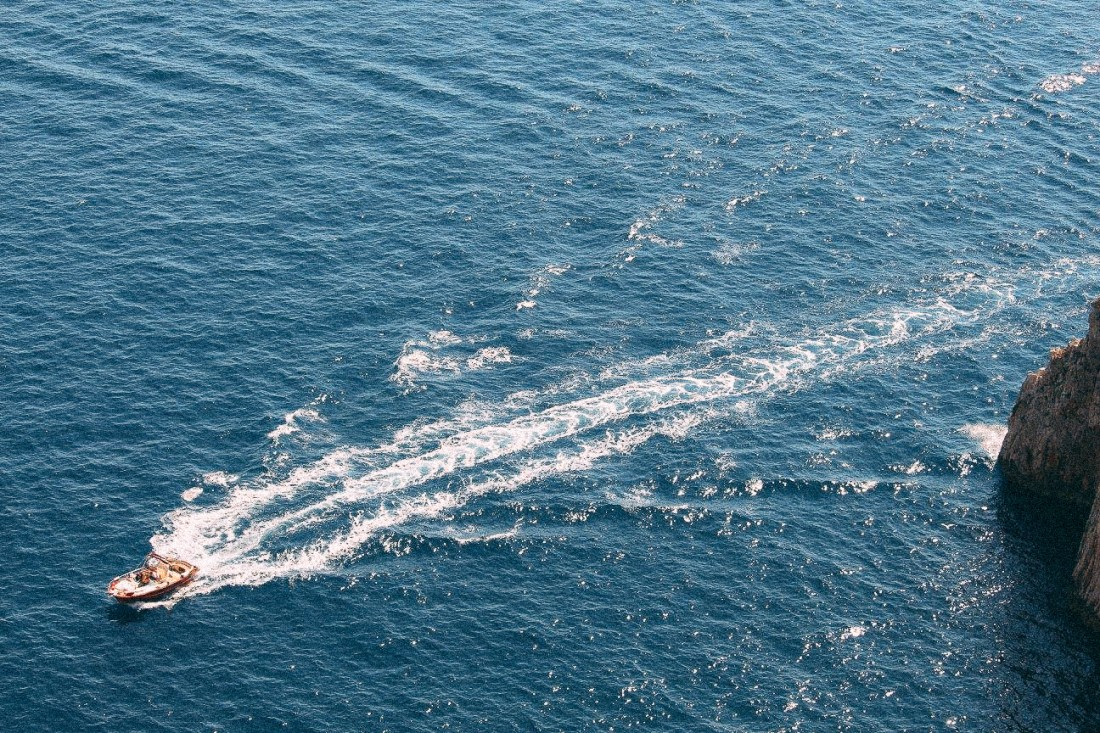 A speedboat whisks through the blue sea surrounding Capri. Travelling from Sorrento to Capri by private boat transfer is possible.