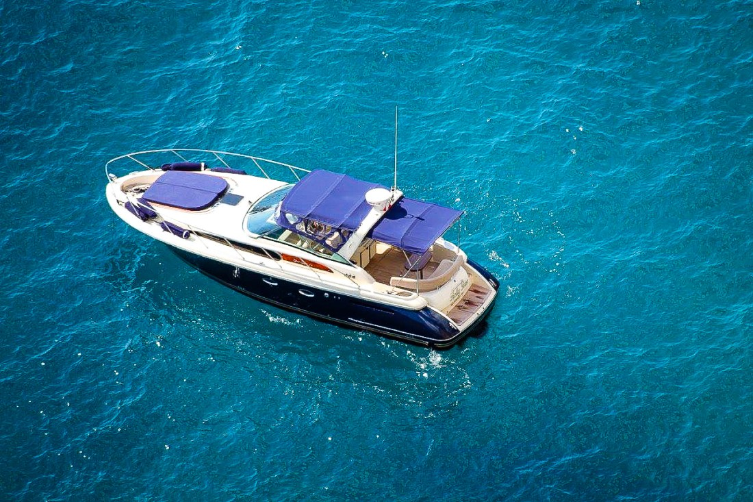 A speedboat in the waters off Capri. The boat is white with a blue roof.