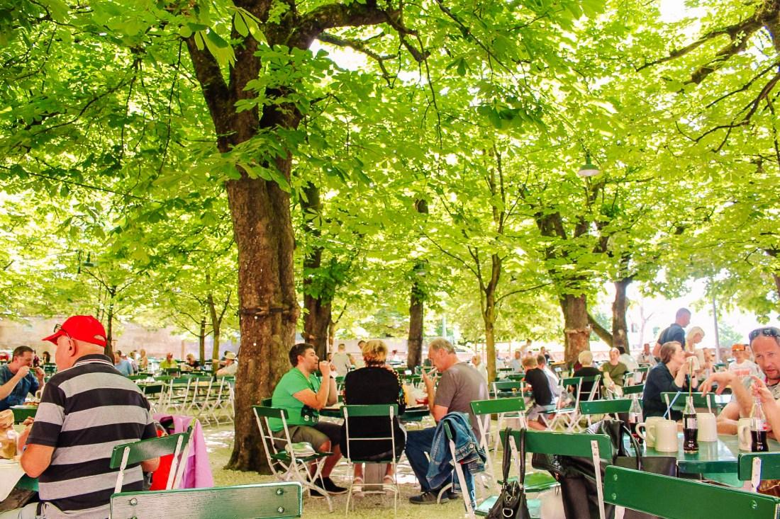 People enjoying sitting under the trees in the Augustinerbrau beer garden. This bierkeller is a great stop before heading from Salzburg to Vienna!