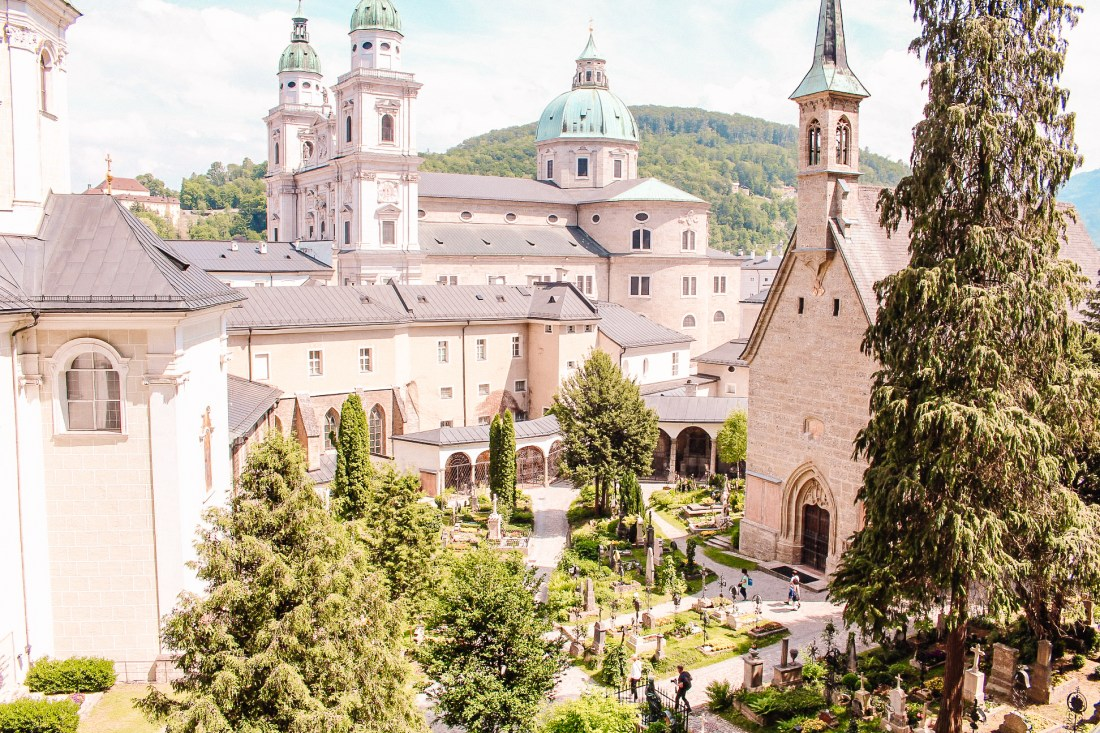 Salzburg's cemetery, with graves and tiered buildings in the background. The cemetery is a tourist attraction, and contains some notable graves.
