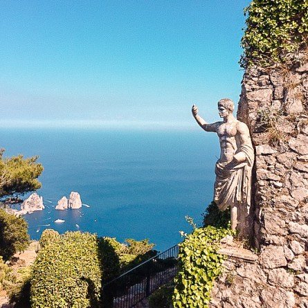 A roman statue stands at the top of Capri's Monte Solaro, with the Faraglioni rocks in the background.