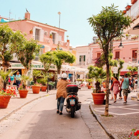 A woman pushes a vespa down Via Roma, one of the most Instagrammable spots in Ischia