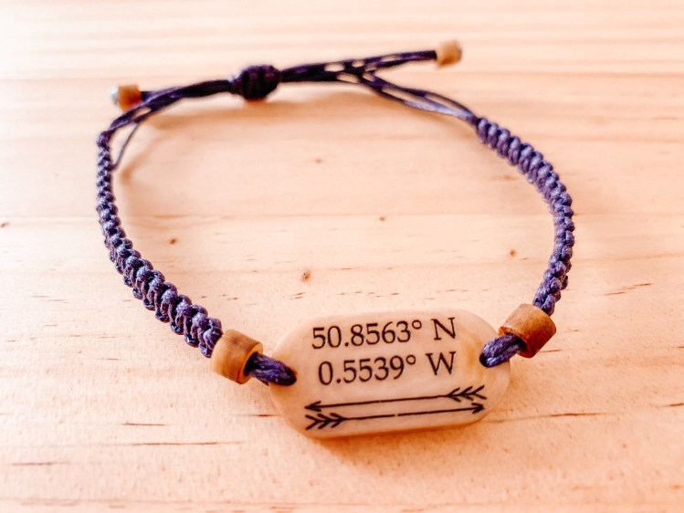 A handmade bracelet from Life Less Ordinary, with a purple band and plate bearing coordinates. This company makes great personalized travel gifts.