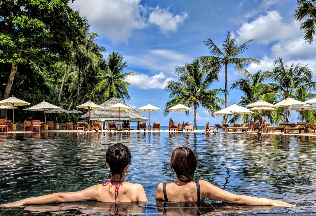 Two women relax in a pool fringed by palm trees. TripIt's travel safety app allows you to check the safety of the area your hotel is located in.