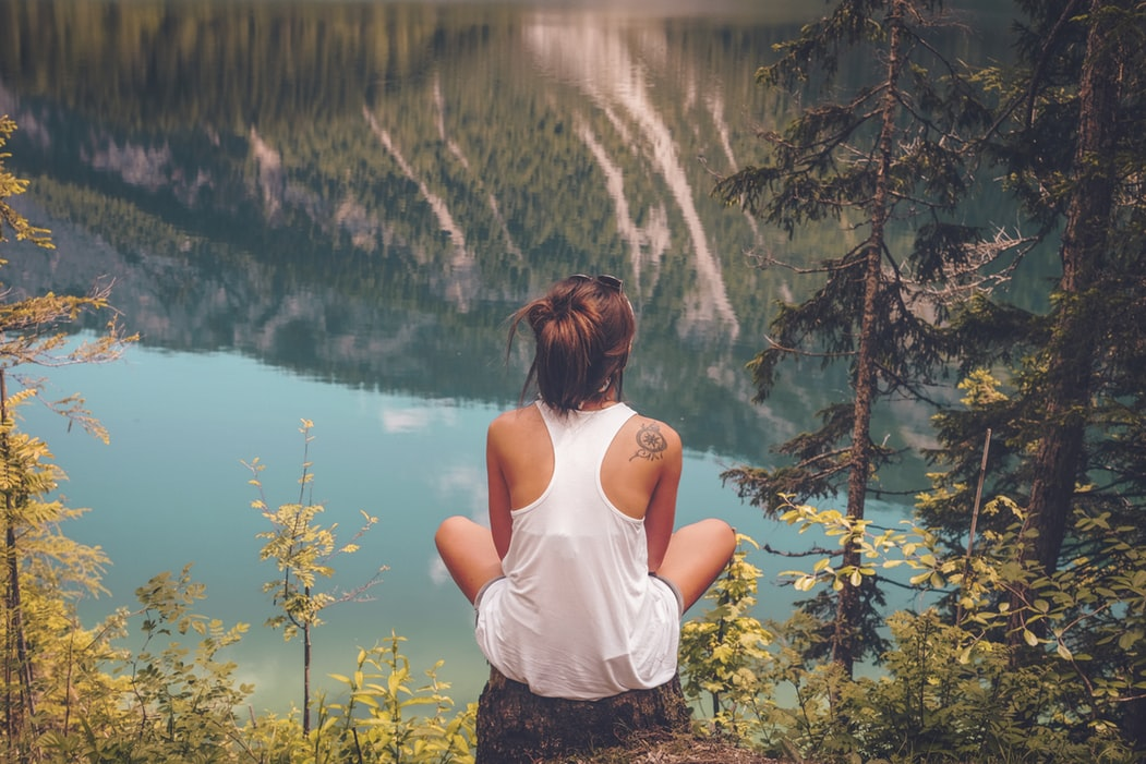 A woman sits alone in the middle of the woods, a lake and mountain ahead of her. A good travel safety app can increase the feeling of safety and wellbeing.
