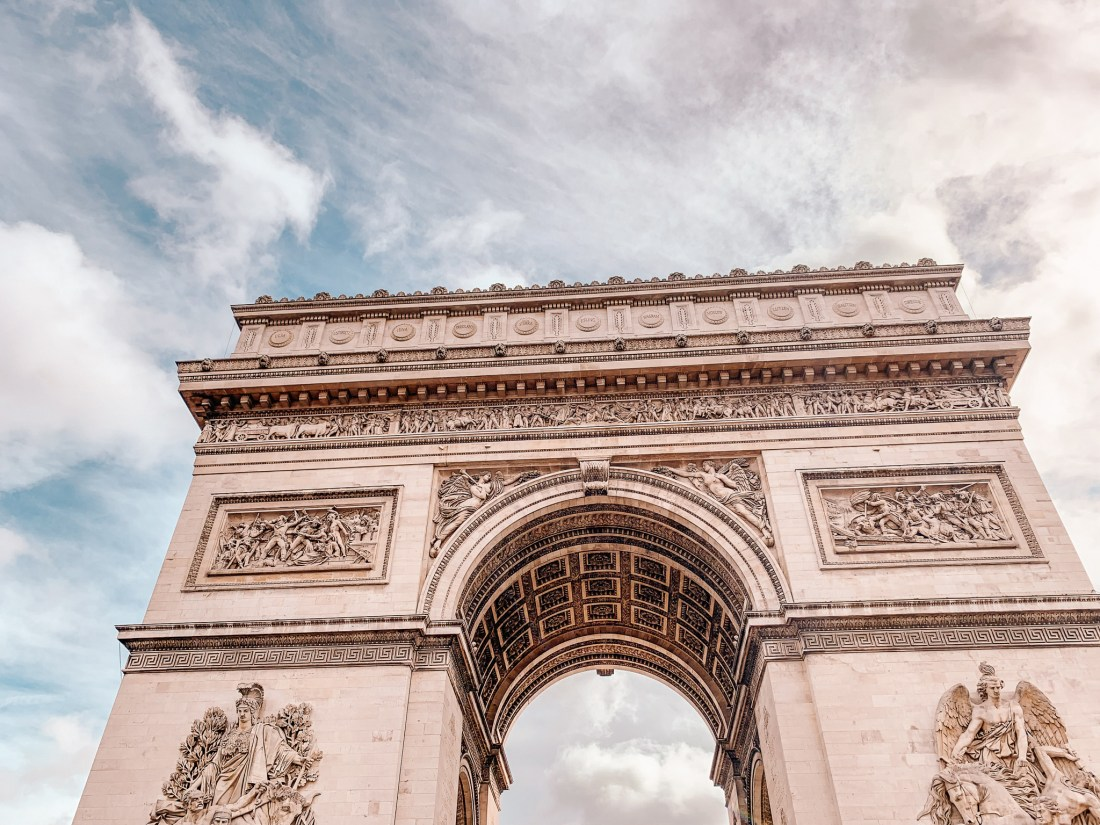 A close up of the Arc de Triomphe in Paris, with its large arch.