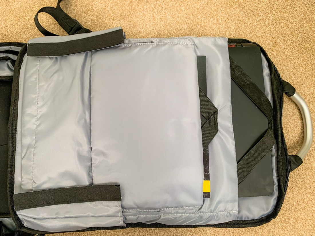 A laptop and a book in the laptop compartment of a backpack