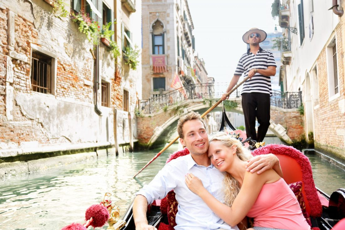 A young couple riding a gondola in Venice, Italy. Italy travel tips will often advise against these, especially if travelling on a budget!