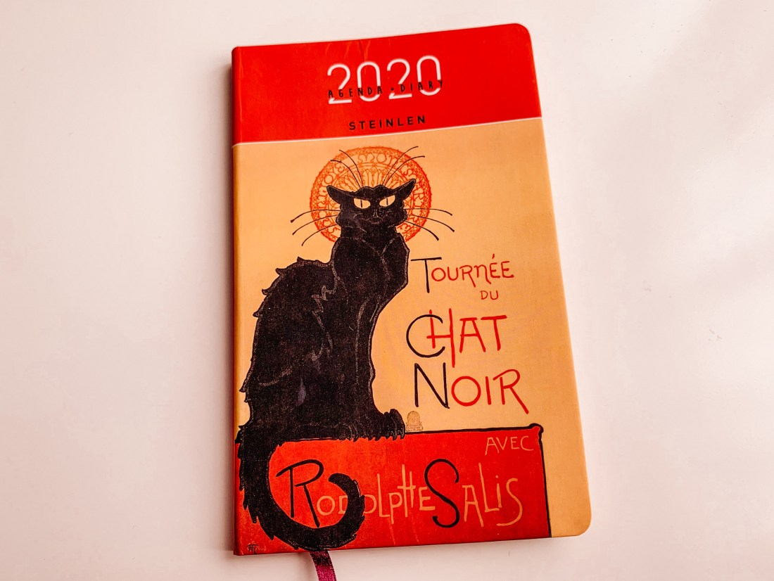 A 2020 Le Chat Noir diary, featuring the famous poster of a black cat.