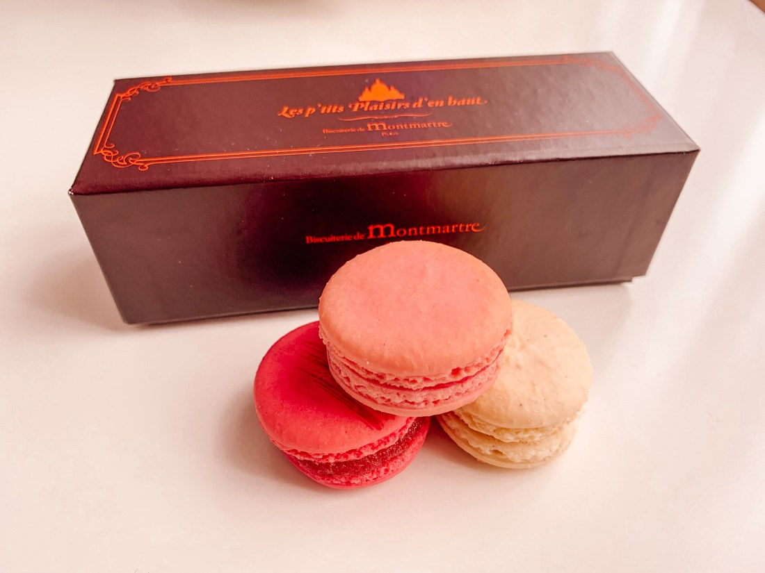 A box of macarons, including pink, red, and white macarons. These are an increasingly popular Paris souvenirs.