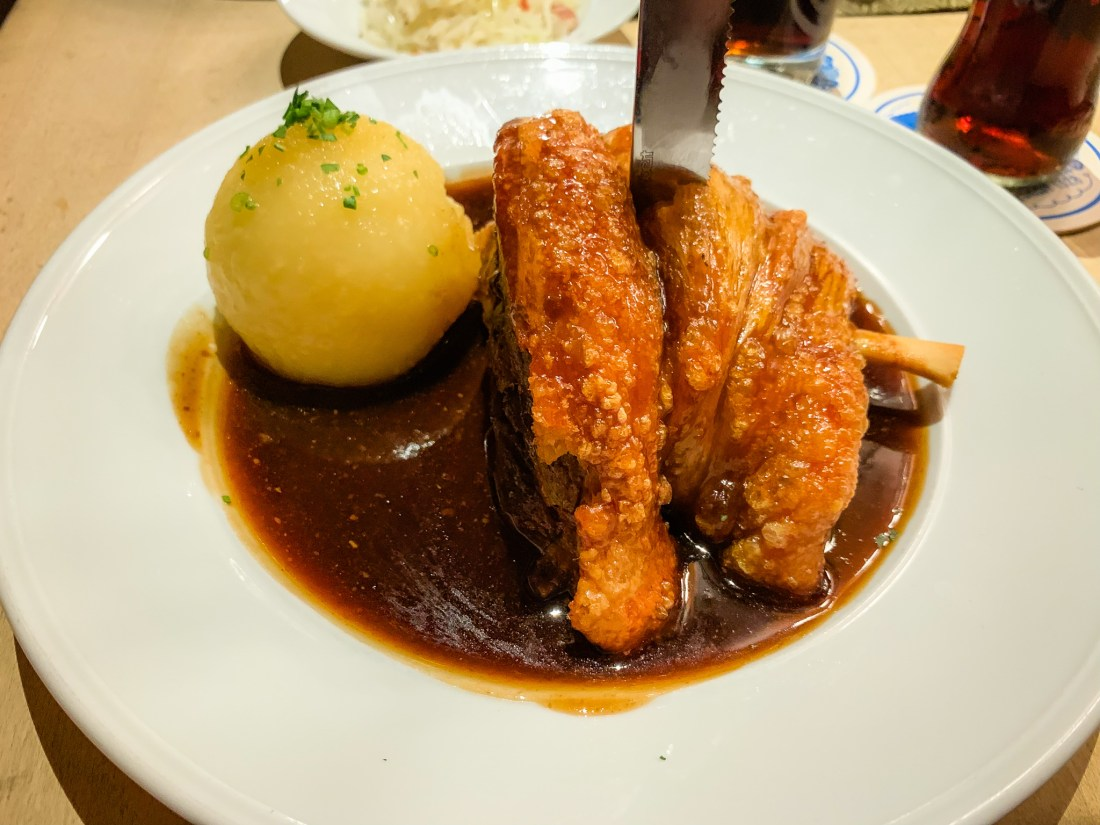 A half pork knuckle on a plate with a potato dumpling on the side, and a knife sticking out of the top. Although seen all over Europe, pork knuckle is a traditional German food.