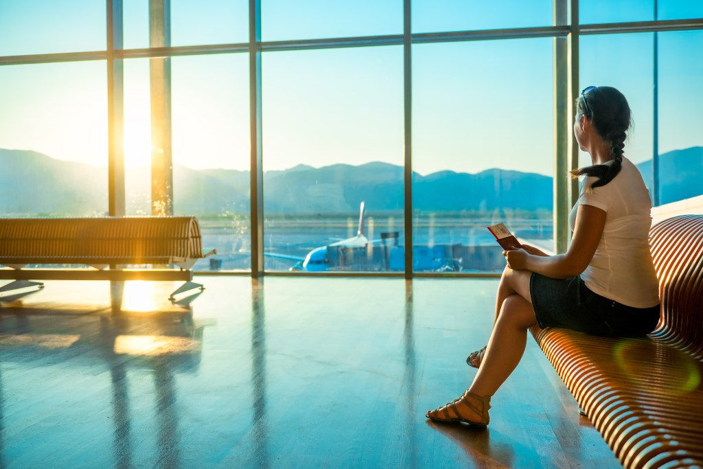 A woman sits in an airport, looking at a plane. Fear of flying commonly causes people to cancel trips.